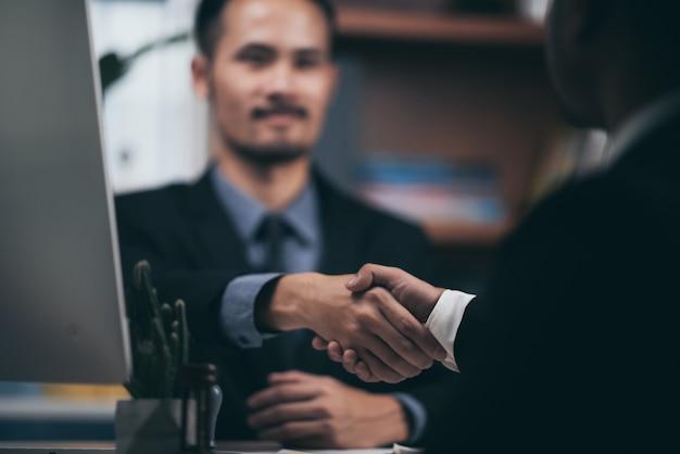 Due uomini sicuri di affari che stringono le mani nel corso di una riunione nel concetto dell'ufficio, di successo, di affare, di saluto e del partner.