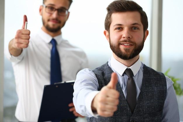 Due uomini sorridenti che mostrano bene nell'ufficio