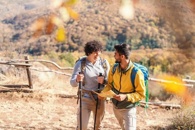 Due uomini sorridenti che parlano mentre stando in natura all'autunno. un uomo che tiene la mappa mentre l'altro tiene bastoni escursionismo in autunno nella natura.