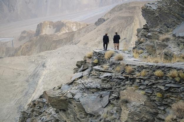 Due uomini stavano parlando lungo il sentiero del ghiacciaio del passu. gilgit-baltistan, pakistan.