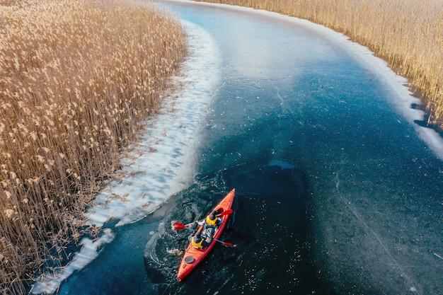 Due uomo atletico galleggia su una barca rossa nel fiume