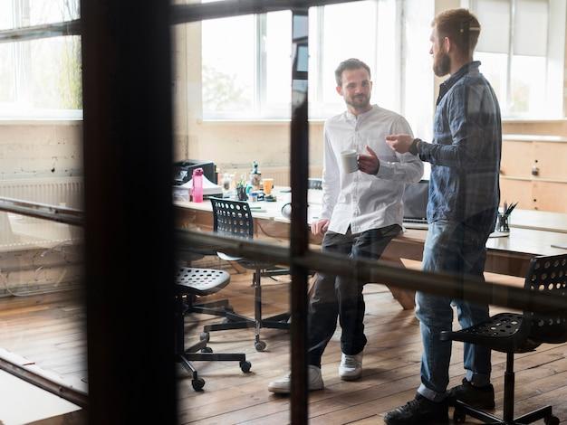 Due uomo d'affari maschio parlando al posto di lavoro
