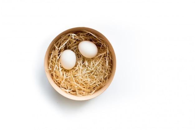 Due uova di pasqua in scatola di legno rotonda isolata su fondo bianco, vista superiore. vacanze pasquali.