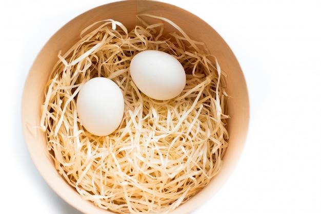 Due uova di pasqua in scatola di legno rotonda isolata, vista dall'alto. vacanze pasquali.