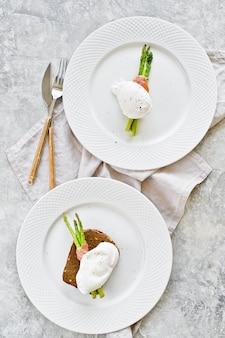 Due uova in camicia su asparagi arrosto avvolto in pancetta.