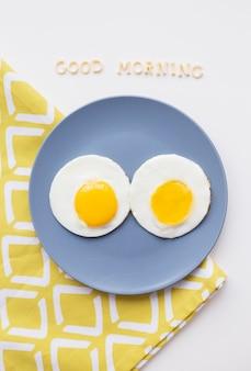 Due uova in camicia su un piatto con buongiorno