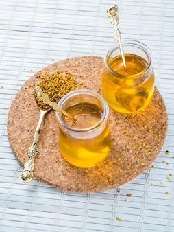 Due vasi di miele con polline d'api su sottobicchiere circolare di sughero sopra tovaglietta