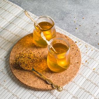 Due vasi di miele con polline d'api su sottobicchiere circolare di sughero