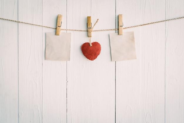 Due vecchi carta vuota e cuore rosso appeso. su sfondo bianco in legno con stile vintage.