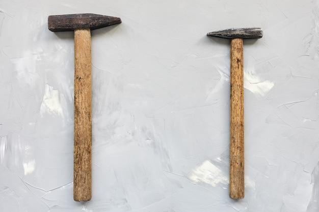 Due vecchi martelli arrugginiti su sfondo grigio