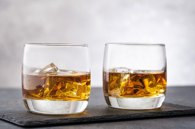 Due vetri con whisky su fondo di pietra grigio