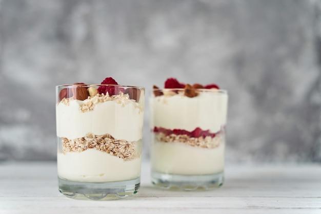 Due vetri del granola greco del yogurt su priorità bassa bianca