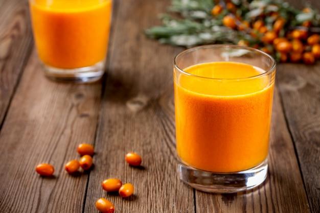 Due vetri del succo urgente fresco dell'olivello spinoso su una tavola di legno.