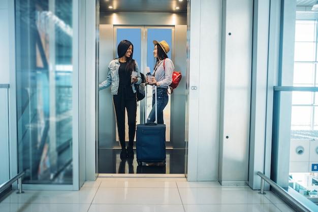 Due viaggiatori femminili con bagagli in ascensore dell'aeroporto. passeggeri con bagaglio in aerostazione