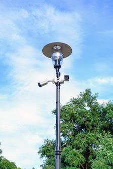Due videocamere di sorveglianza bianche sulla posta della lampada del metallo su cielo blu