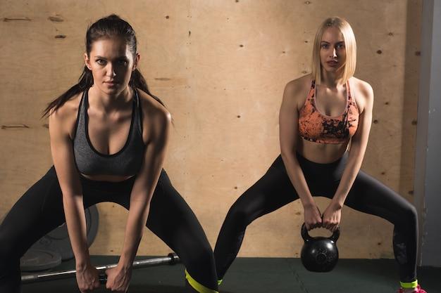 Due womans atletici che si esercitano con la campana del bollitore mentre si trovano in posizione tozza
