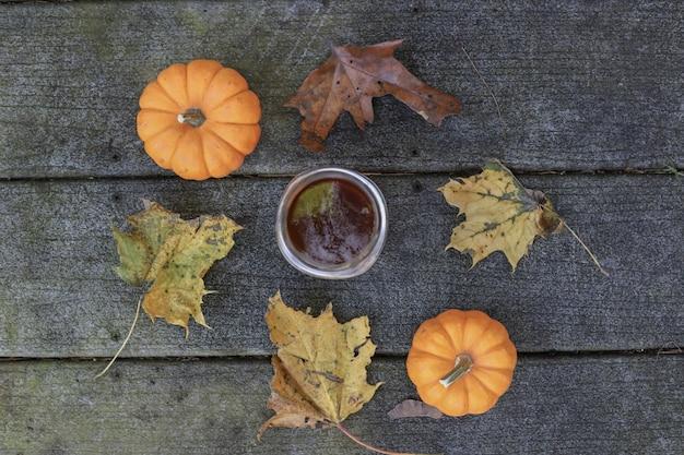Due zucche e foglie che circondano la tazza