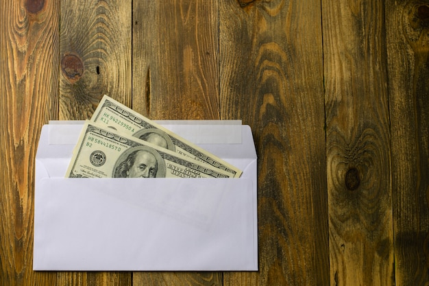 Duecento dollari in cento dollari in contanti in busta bianca giacciono sul tavolo di legno marrone.
