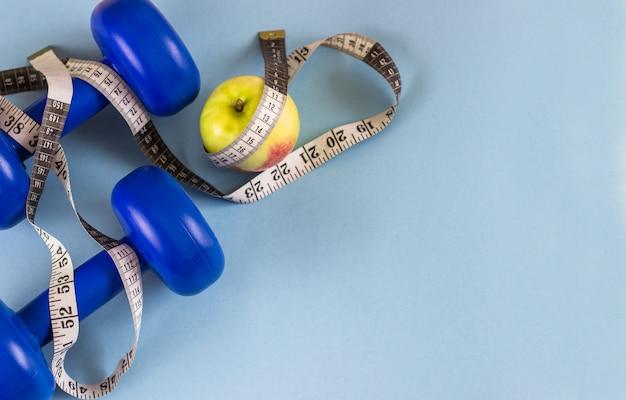 Dumbbells blu, nastro di misurazione e mela su una priorità bassa blu. si preoccupa per il corpo.