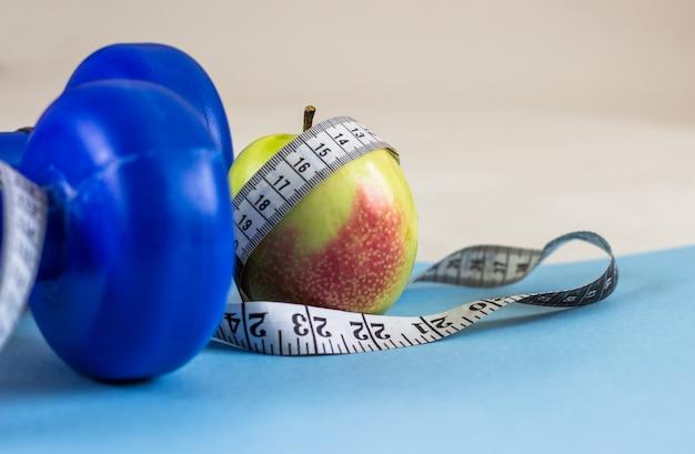 Dumbbells blu, nastro di misurazione e mela su una priorità bassa blu. uno stile di vita sano