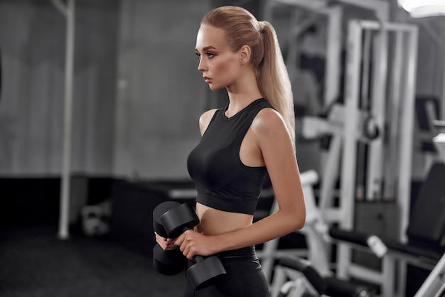 Dumbbells d'innalzamento biondi motivati in ginnastica.