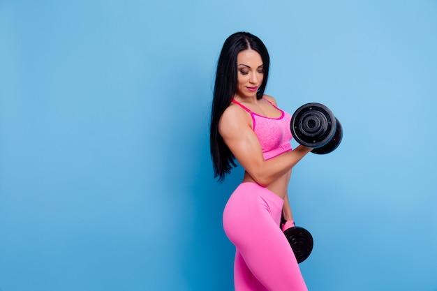 Dumbbells muscolari della holding della donna
