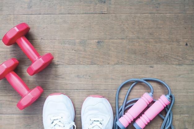 Dumbbells rossi, salto corda e scarpe sportive su sfondo di legno con copia spazio, concetto di stile di vita sano