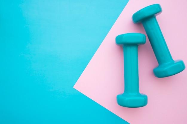 Dumbbells su sfondo blu e rosa