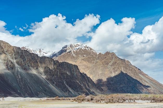 Duna di sabbia del dessert con cielo blu nuvoloso, valle di nubra in leh ladakh, india del nord
