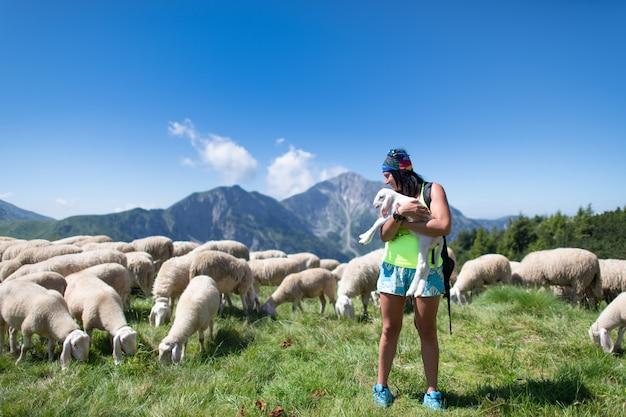 Durante il trekking, una ragazza tiene in braccio un agnello appena nato