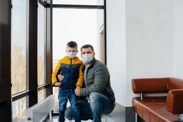 Durante la quarantena, un padre con il figlio si trova in una maschera. pandemia, coronavirus
