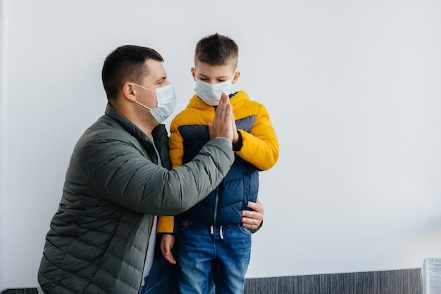 Durante la quarantena, un padre con il figlio si trova in una maschera. pandemia, coronavirus.