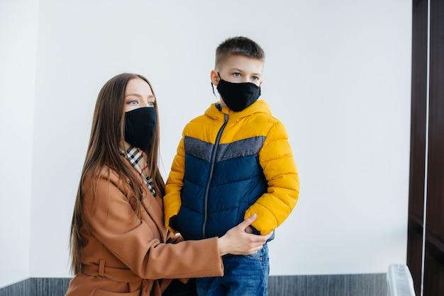 Durante la quarantena una madre con il suo bambino si trova in una maschera. pandemia, coronavirus