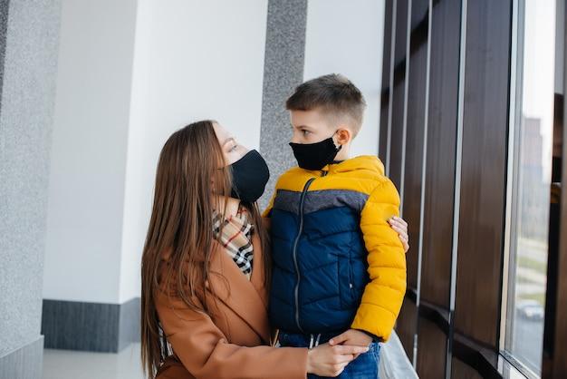 Durante la quarantena una madre con il suo bambino si trova in una maschera. pandemia, coronavirus.