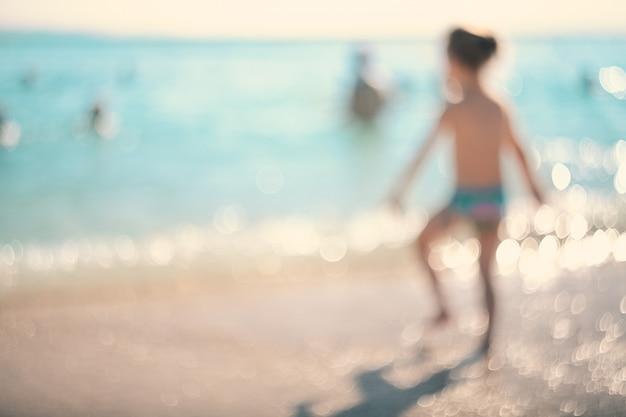Durante le vacanze estive. silhouette di una ragazza che corre nel mare.