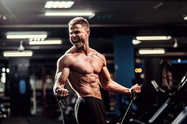 Duro atleta ben costruito che si esercita con una fascia di resistenza