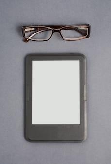 E-book e occhiali su grigio