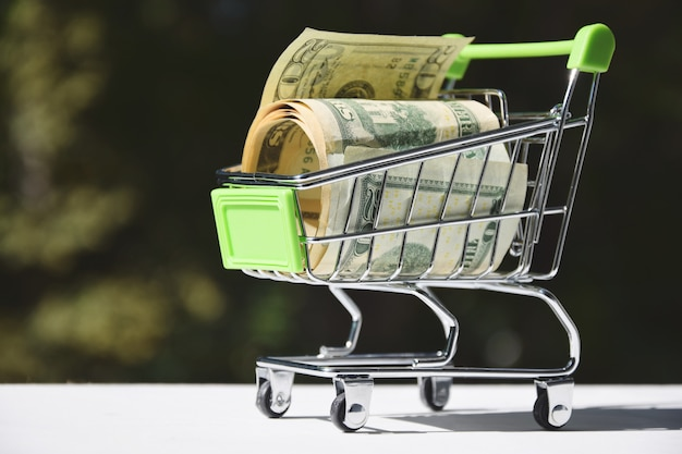 E-concept, banconote da un dollaro nel carrello del supermercato.