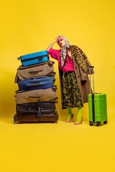 È difficile essere influencer. un sacco di vestiti per viaggiare. ritratto della donna caucasica su sfondo giallo. bellissima modella bionda. concetto di emozioni umane, espressione facciale, vendite, annuncio.