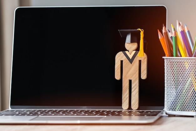 E-learning online back to school concept persone in legno con la laurea che celebra il cappuccio sul computer