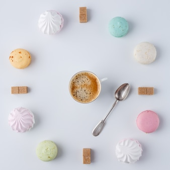 È ora di bere caffè, un orologio a forma di caffè, macarons, zucchero, marshmallows,