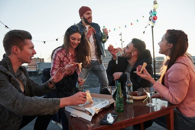 È tempo di cantare. almeno un ragazzo con il cappello rosso la pensa così. mangiare la pizza alla festa sul tetto. i buoni amici hanno un fine settimana con del cibo e alcol deliziosi