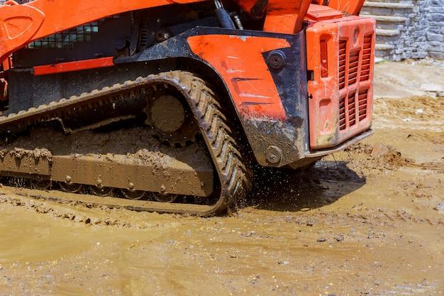 È trattore della costruzione che funziona con il mucchio di terra