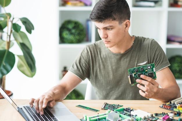 È un tecnico che ripara l'attrezzatura hardware guardando il portatile