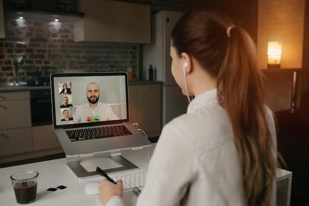 Earview della donna di affari in una videoconferenza con il suo capo e colleghi durante una riunione online. uomo in una videochiamata con i partner.