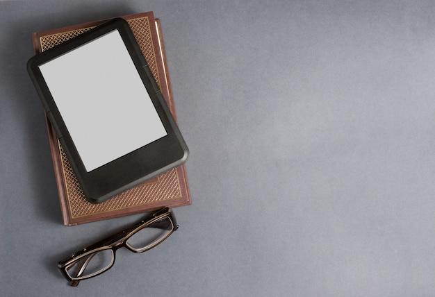 Ebook, libro e occhiali su grigio