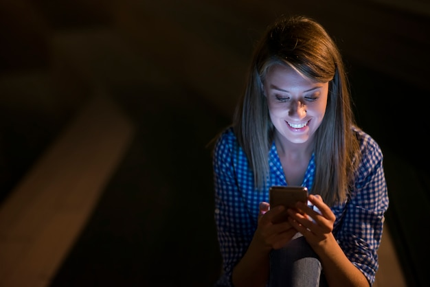 Eccita bella ragazza che riceve un messaggio sms con buone notizie in un telefono cellulare all'esterno