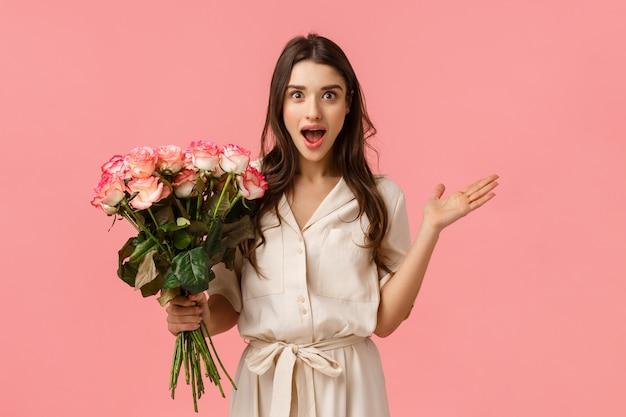 Eccitata e divertita, stupenda donna moderna stupenda in abito alla moda, allarga le mani lateralmente stupita e stupita, sbalordita da un bel gesto, con graziosi fiori, bouquet di rose