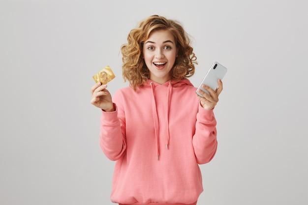 Eccitata ragazza dai capelli ricci sorridente che mostra la carta di credito, pagando per l'ordine online tramite smartphone