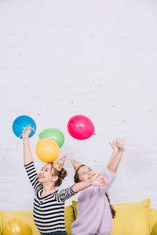 Eccitati adolescenti che sollevano le mani tenendo palloncini colorati